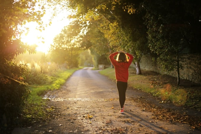 Woman taking an early morning walk on a country road