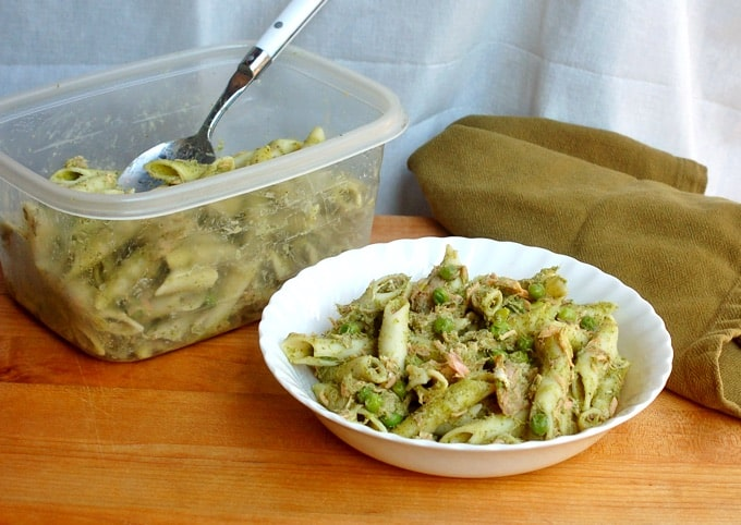 White bowl with penne pasta, smoked salmon and peas on a table next to a Tupperware container with more pasta