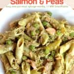 Penne pasta with smoked salmon and peas in white dinner plate.