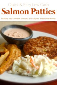 Salmon patty with cole slaw, potato wedges and horseradish sauce on white dinner plate.