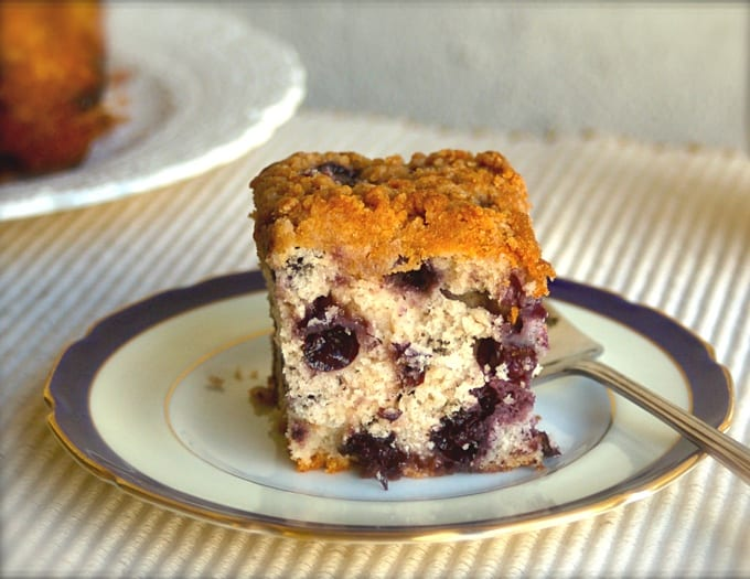 Piece of blueberry crumb cake on small plate with fork.