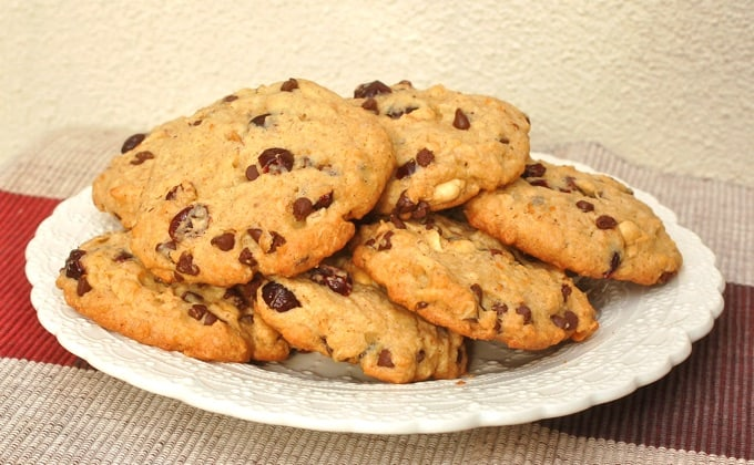 Plate full of trail mix cookies with chocolate chips, dried cranberries and peanuts