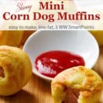 Mini Corn Dog Muffins on a wood cutting board with a small dish of ketchup and one muffin has a bite taken out of it
