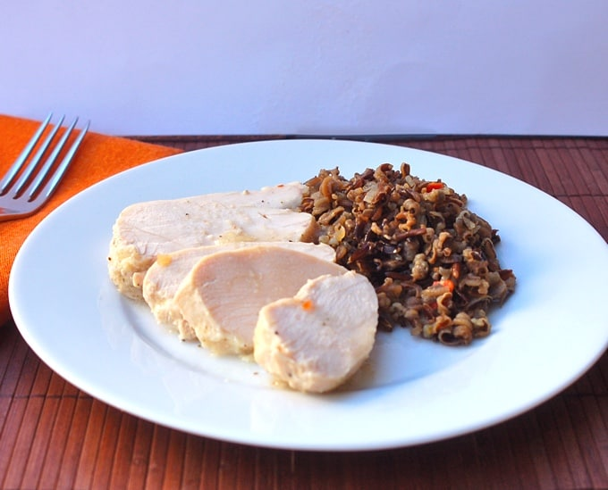 Slices of chicken breast with wild rice salad on white dinner plate
