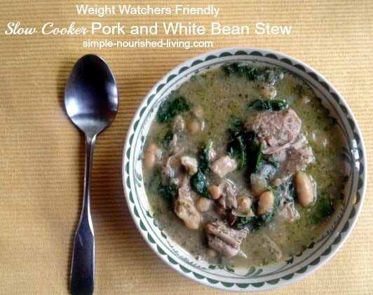 Slow Cooker Pork and White Beans Stew in a bowl with spoon alongside