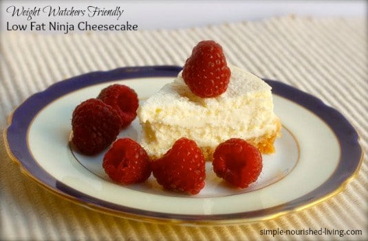 Slice of cheesecake topped with fresh raspberries on blue and white dessert plate.