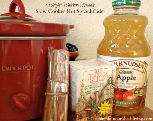 Ingredients for making spiced apple cider including a red crock pot, cinnamon stocks, mulled spice tea bags and bottle of organic apple juice.