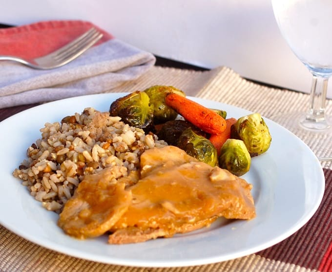 Sliced Teriyaki pork roast on white dinner plate with roasted Brussels sprouts, carrots and brown rice with lentils.