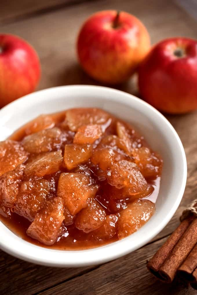 Apple compote in small white bowl with fresh apples and cinnamon sticks off to the side.