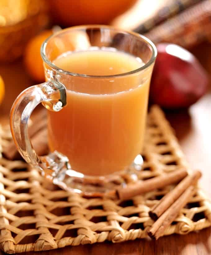 Hot spiced apple cider in glass mug on woven mat with cinnamon sticks, apples and pumpkins in the background.