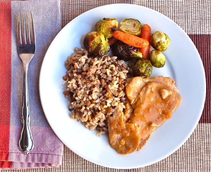 Teriyaki pork roast with roasted Brussels sprouts, carrots and brown rice with lentils on white dinner plate with fork.
