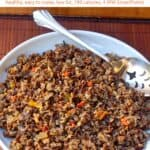 Crockpot cooked wild rice in white serving dish with serving spoon on wooden mat.
