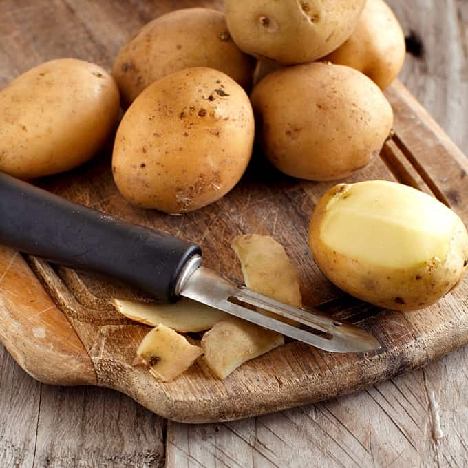 Peeling raw potatoes with a vegetable peeler on wooden cutting board.