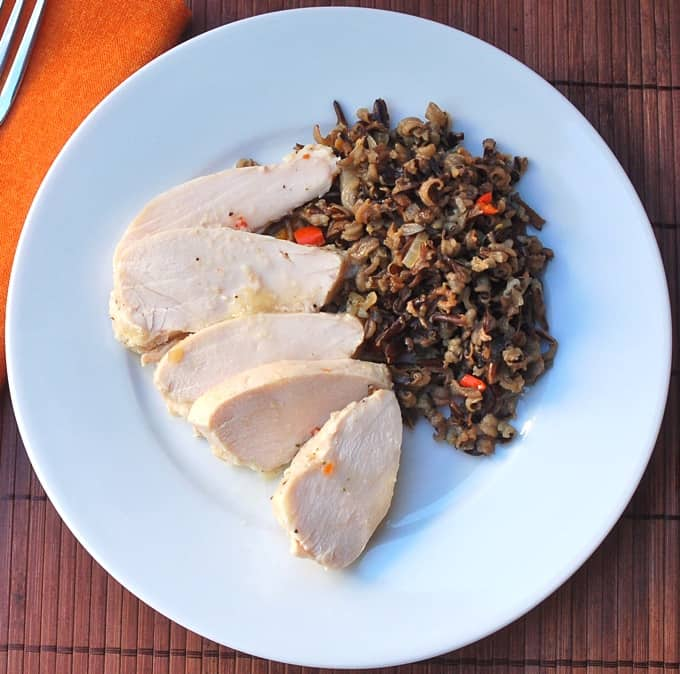 Sliced chicken breast with wild rice on white plate