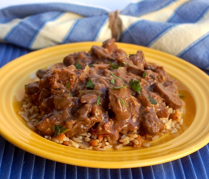 Beef with mushroom sauce over rice on yellow dinner plate.