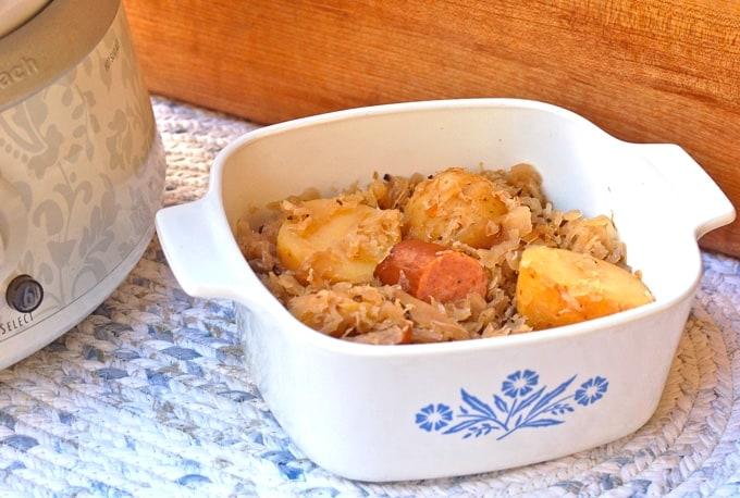 Turkey kielbasa, sauerkraut and potatoes in casserole dish next to slow cooker.