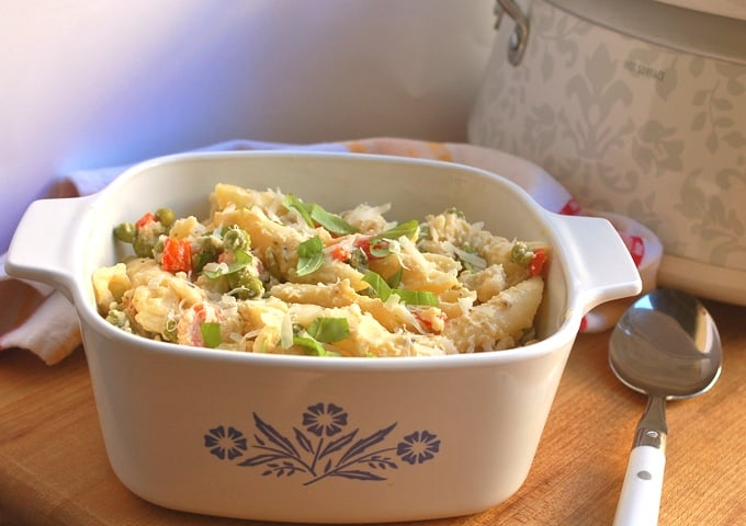 Casserole dish with creamy slow cooker pasta prima vera with serving spoon and crock pot in the background.