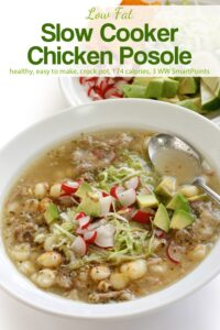 Bowl of chicken posole soup topped with shredded cabbage, chopped radish and avocado.
