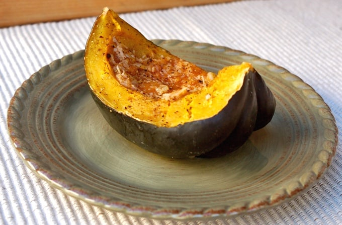 Wedge of acorn squash with mango chutney and coconut on green dinner plate.