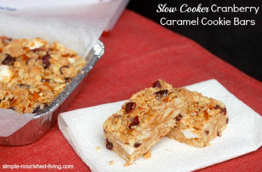 Two Cranberry Caramel Cookie Bars sitting next to the pan of bars