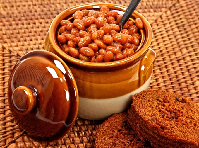 Baked Beans in Ceramic Bean Pot with Brown Bread On Placemat