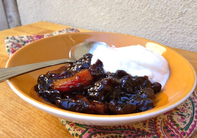 Crock pot dried fruit compote with yogurt in yellow bowl with a spoon.