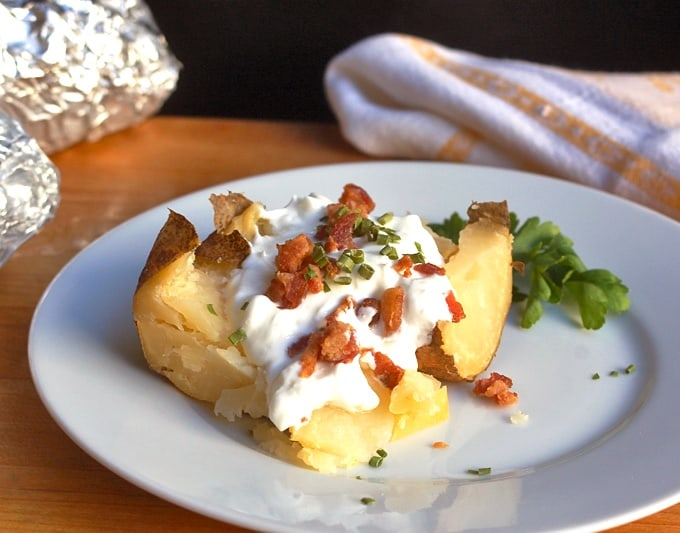 Crock pot baked potato with sour cream and chopped bacon on white plate with two foil-wrapped potatoes in background.