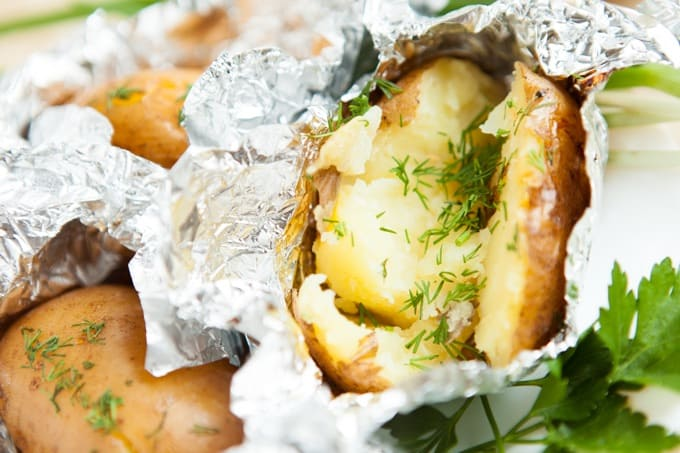 Crock pot baked potatoes with dill wrapped in foil, close up