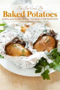 Two aluminum foil wrapped baked potatoes with fresh herbs on white plate.