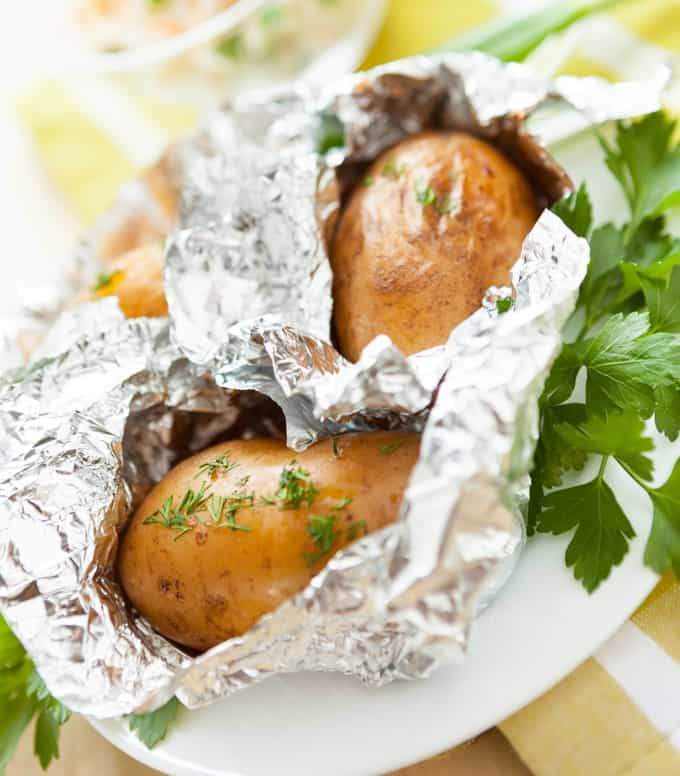 Two foil-wrapped baked potatoes with fresh herbs on white plate.