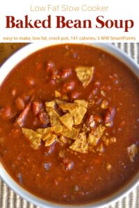 Bowl of baked bean soup topped with crushed tortilla chips up close.