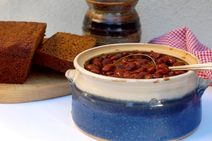 Homemade baked beans in a ceramic crock with brown bread in the background