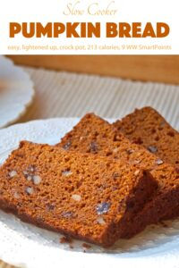 Fresh sliced pumpkin bread with raisins and nuts on a white plate.