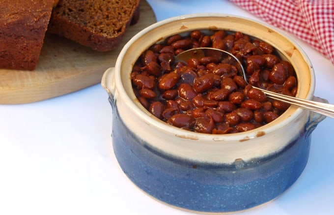 Baked Beans in a ceramic crock with a spoon and dark molasses bread in the background