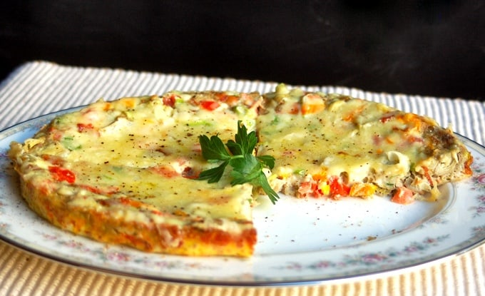 Whole vegetable frittata with on flowered serving plate slice cut out.