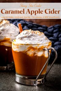 Two glasses of caramel apple cider with whipped topping and cinnamon stick.