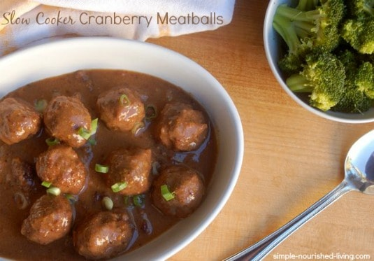 Slow Cooker Cranberry Meatballs in white dish with spoon and bowl with roasted broccoli.