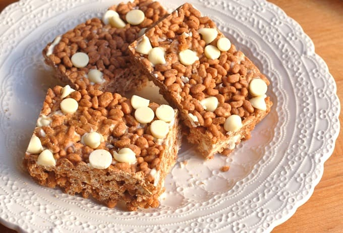 Three crispy caramel mocha crunch bars with white chocolate chips on a white plate