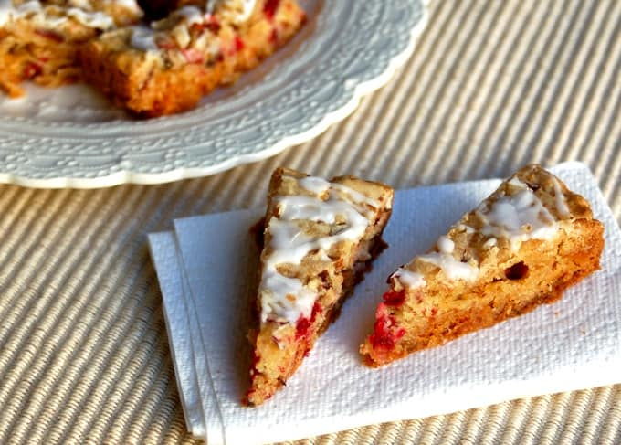 Crock pot cranberry white chocolate cookies bars sitting on white napkin with serving platter in the background.