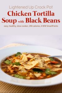 Chicken tortilla black bean soup garnished with fresh cilantro and crushed tortilla chips in white bowl with spoon.