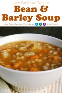Slow cooker bean and barley soup in white bowl up close.