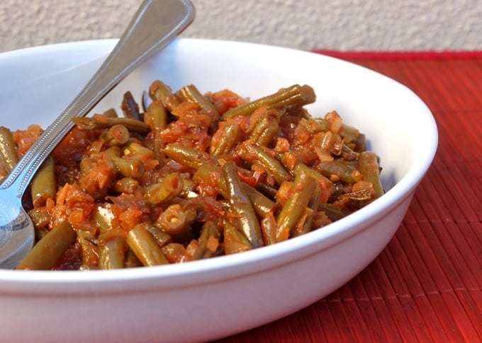 Creole-Style Green Beans in a white serving dish with a spoon