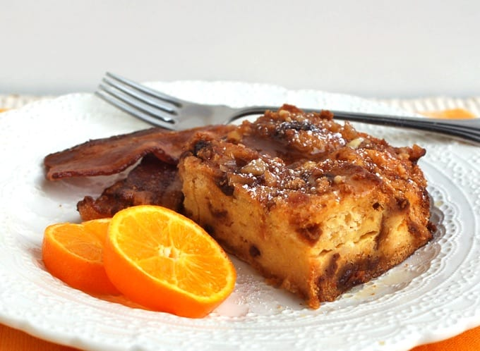 Eggnog French Toast Casserole on a white plate with bacon and fresh orange slices