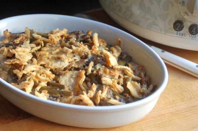 Slow cooker green bean casserole topped with french fried onions in white serving dish near crock pot.