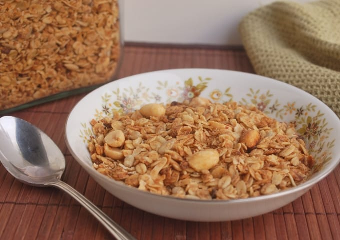 Slow cooker peanut butter granola in bowl with spoon and green napkin on wooden mat.