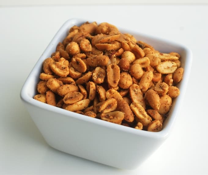 Spicy peanuts in square white bowl up close.