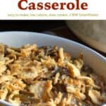 Slow cooker green bean casserole topped with crispy french fried onions in white serving dish near crock pot.