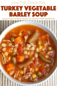 Crock pot turkey vegetable barley soup in white bowl from above.