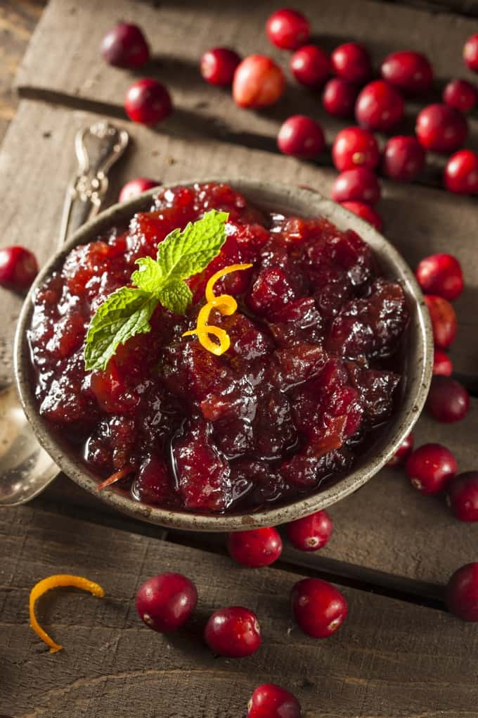 Small bowl of whole cranberry sauce on a wooden table