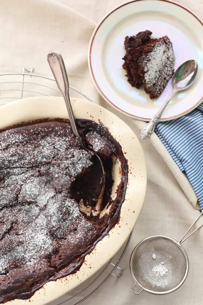 Warm chocolate pudding cake in a large crock pot with a small serving on a small white plate